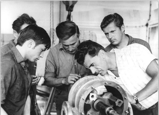vintage blue collar workers working on engine pieces
