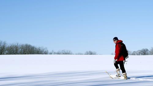 man walking across prairie on snowshoes