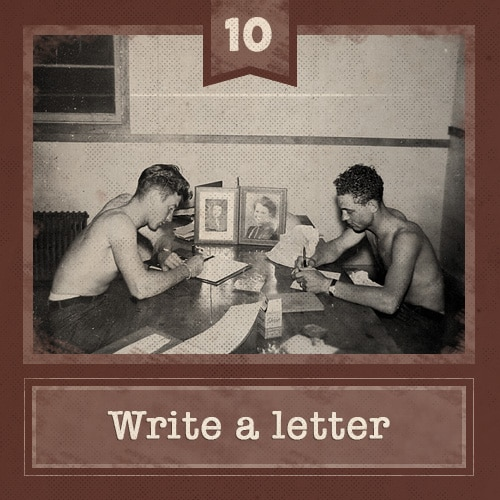 Vintage men sitting at table shirtless writing letters.