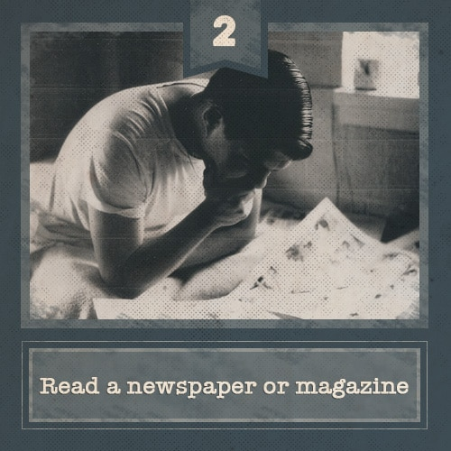 vintage young man sitting on bed reading newspaper