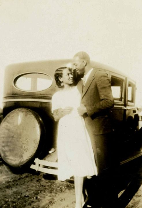 Vintage couple standing in front of car.