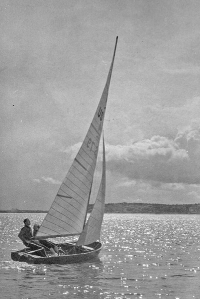 vintage man in sailboat on lake