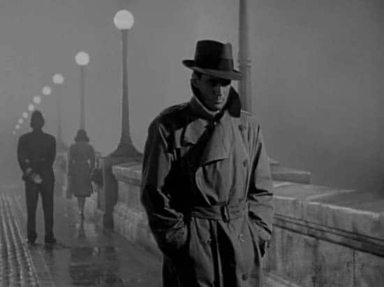 vintage man walking across bridge in trench coat