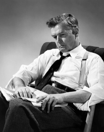 vintage man in chair looking sad depressed newspaper in lap