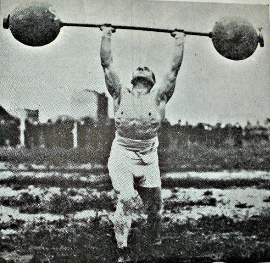 Vintage man strongman lifting heavy barbell overhead press.