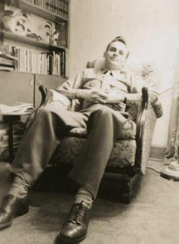 Vintage man sitting in chair arms folding on lap.