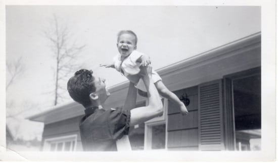 Vintage father holding son upside infront of house .