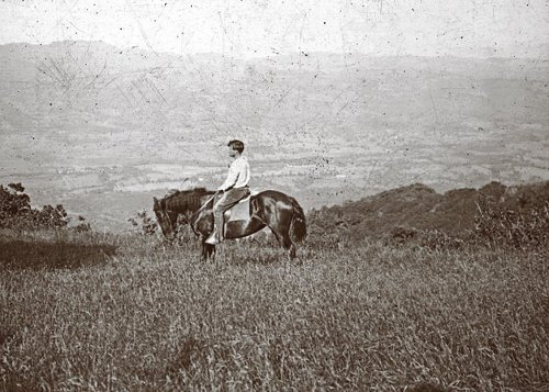Jack London riding the horse in the field.