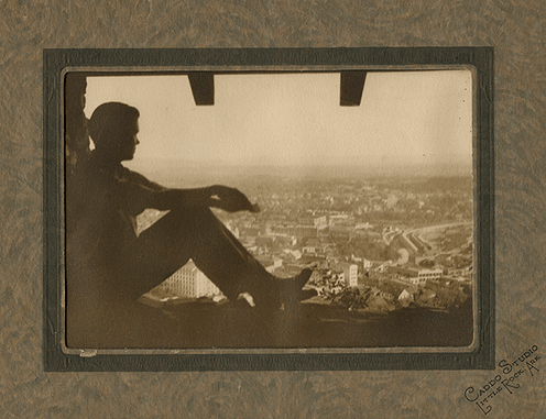 Vintage man sitting in window starting out over city.