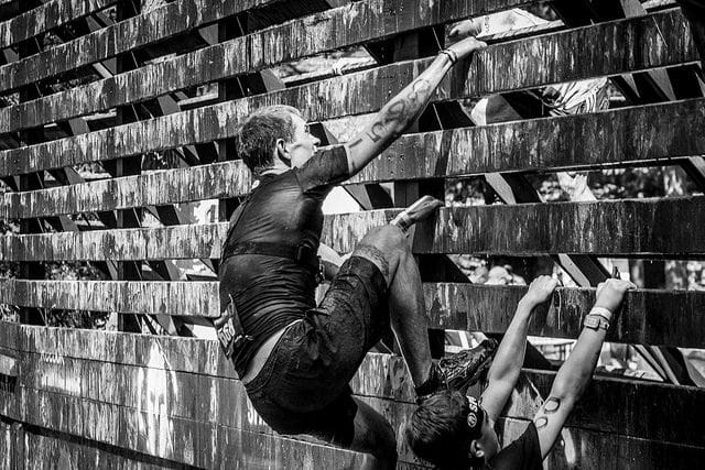 man climbing wall during obstacle race