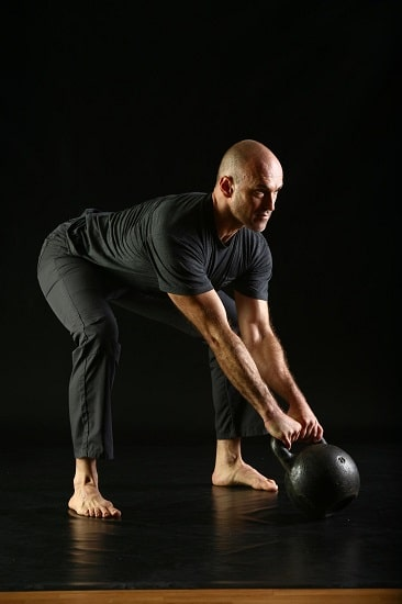 A man doing kettlebell weight lifting.