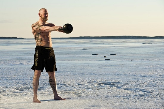A man doing kettlebell swing near the sea.
