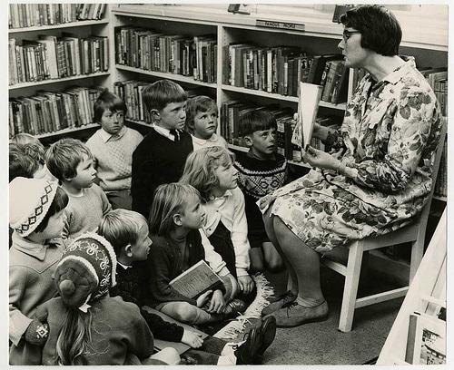 Vintage teacher reading book to kids on floor.