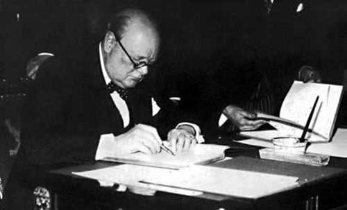 Winston Churchill sitting at desk and writing with fountain pen.