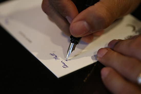 A man using fountain pen to write at the corner of paper.