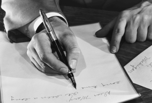 A man using fountain pen to write on paper.
