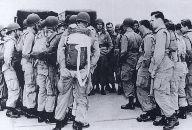vintage paratroopers in group wearing backpacks being briefed