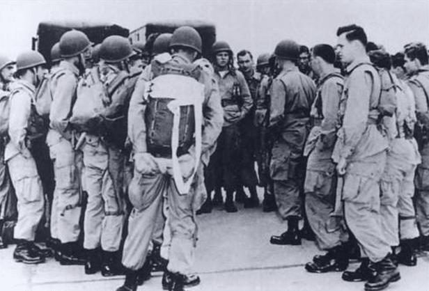 vintage paratroopers in group wearing backpacks being briefed