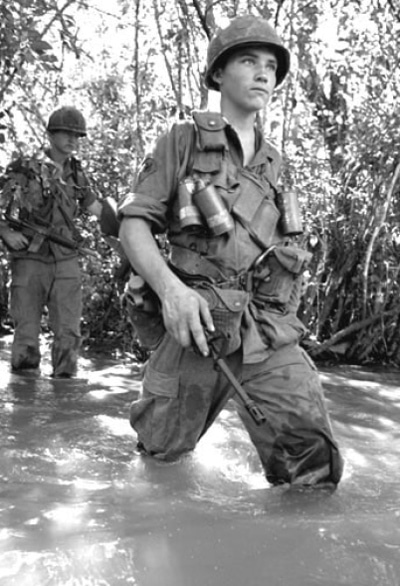 Soldier in vietnam wading through river.