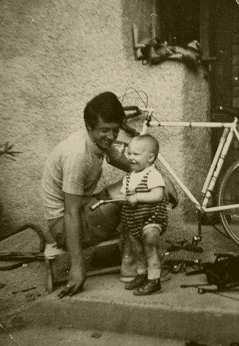 vintage cyclist father with bike and baby