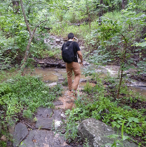 man hiking rucking over muddy river