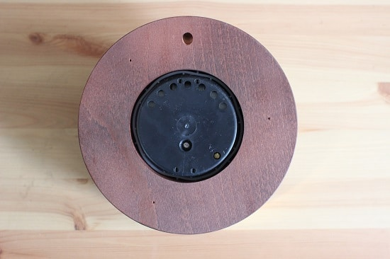 The back of an aneroid barometer. The holes at the top of plastic backing allow for air to flow through. The small screw on the bottom right edge is what's used to calibrate the device; I had to use a small eyeglass screwdriver to do so.