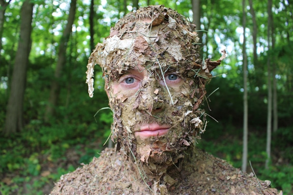 Man face covered with forest debris natural camouflage.