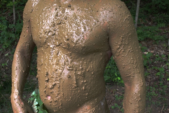Man covered in mud for camouflaging.