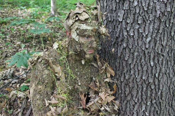 Man camouflaged with tree.