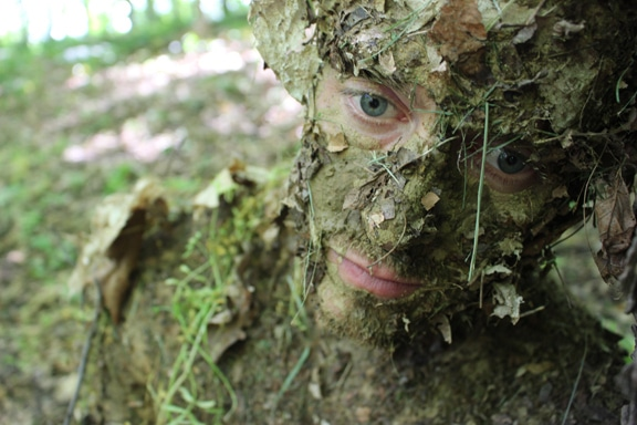 Men face camouflage with mud and leaves.