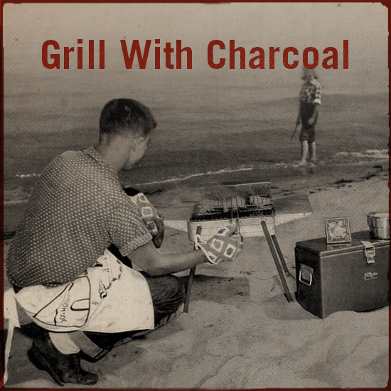 A man is grilling with charcoal.