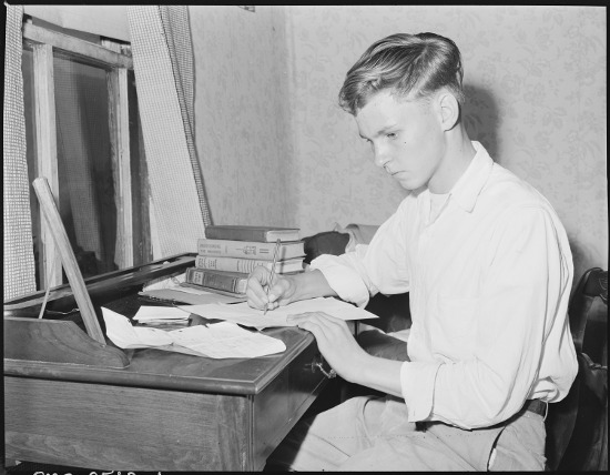 young man writing essay on paper 1950s 1940s