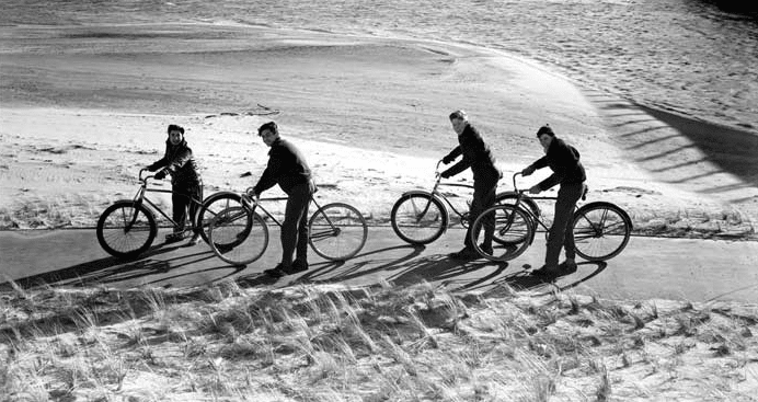 vintage young men riding bikes beach winter