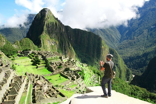 Traveler taking picture with cell phone in Machu Picchu, Peru
