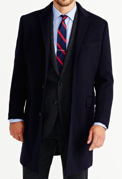 man wearing overcoat over suit and tie