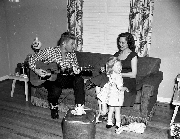 vintage man playing guitar for wife daughter in house