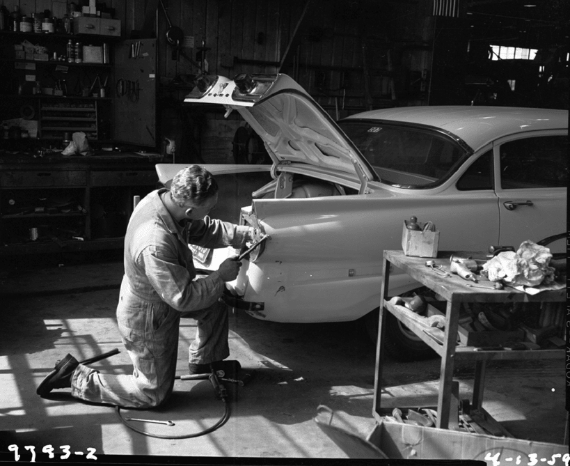 vintage auto mechanic working on 50s car in garage