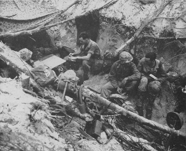 wwii soldiers in trench sitting talking