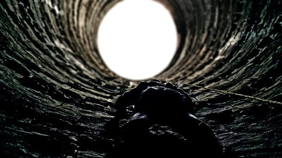 man climbing out of pit well looking up