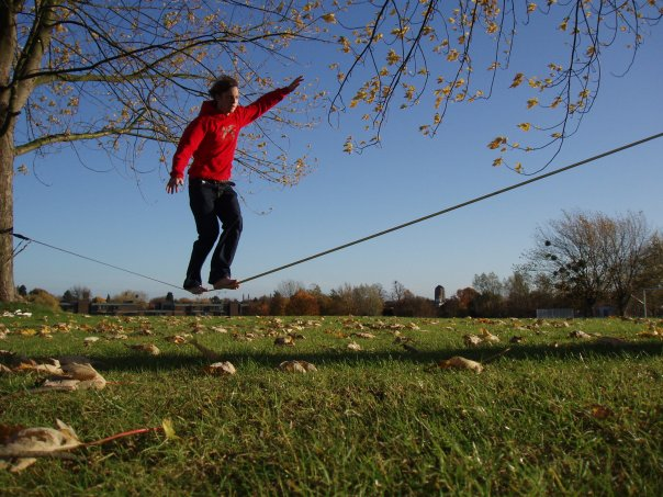 young man slacklining between trees open grass field