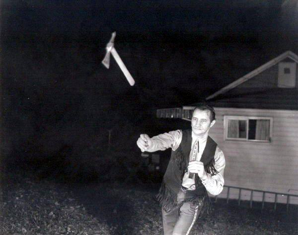 vintage man throwing tomahawk ax mid-air