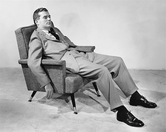 vintage man in suit loafing in mid century chair
