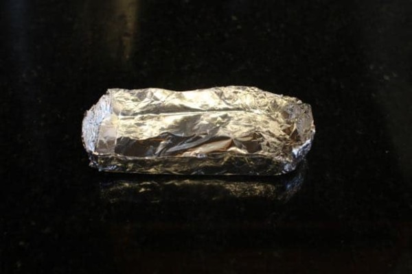 Aluminum foil container for smoke bomb on a black marble.