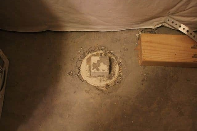 A sewer line clean out in the floor of a basement storage area.