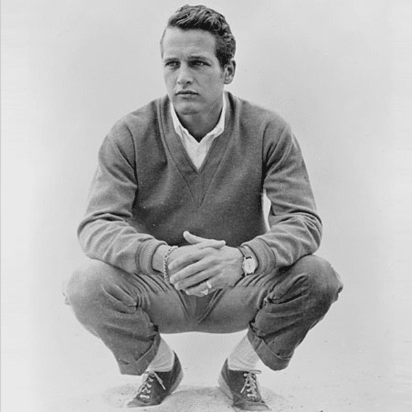 paul newman squatting on ground sweater khakis