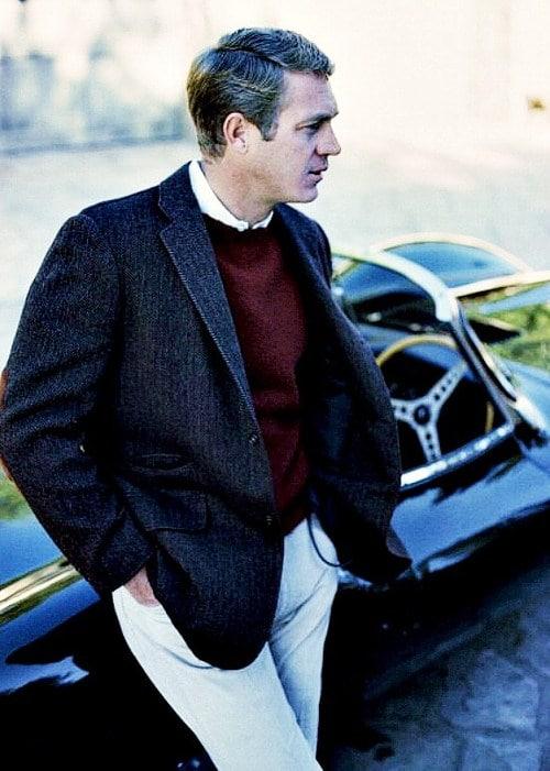 older steve mcqueen khakies sports coat standing next to car