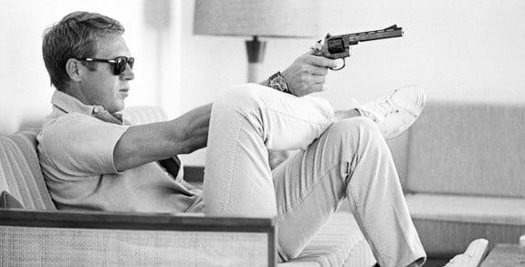 steve mcqueen pointing gun wearing khakis