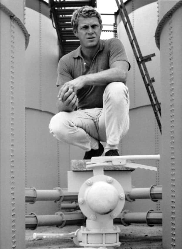 steve mcqueen squatting sitting on navy ship