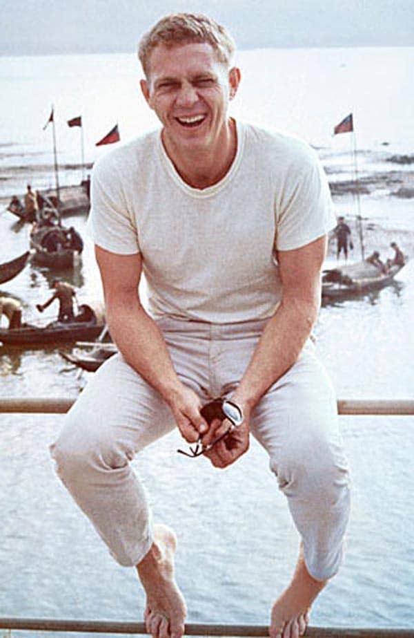steve mcqueen sitting smiling on railing next to ocean