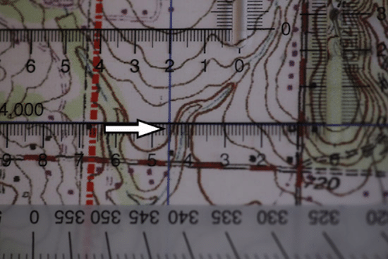 Land navigation lining up protractor and topo topographic map.